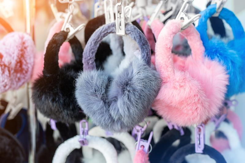 Lot of many multicolored bright fluffy warm winter fur earphones and gloves hanged on rack at store display for sale. Cute cold. Season clothes accessories royalty free stock photography