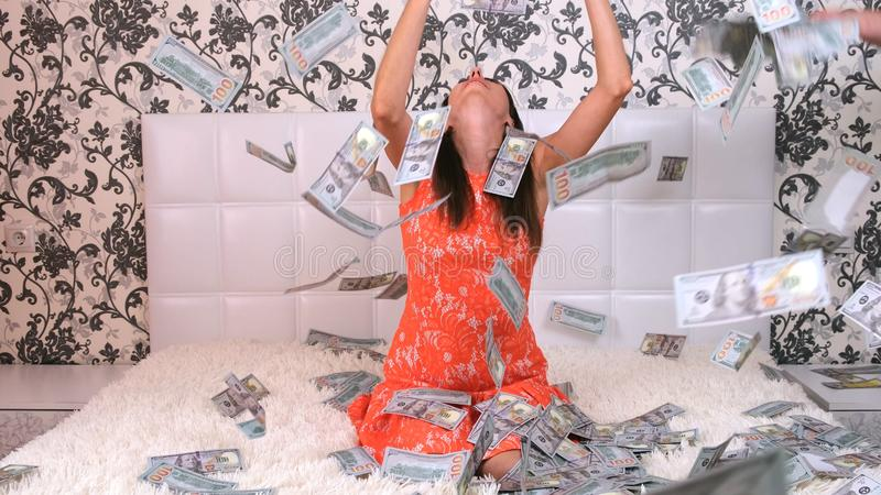 Lot of money flies in the air over a white bed with a beautiful girl. The concept of tremendous wealth. stock image