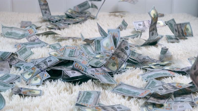 A lot of money, a view from the top, a girl in a cropped dress collects them. Throws, rejoices. Lies in the money they. Fall on her from the top stock images