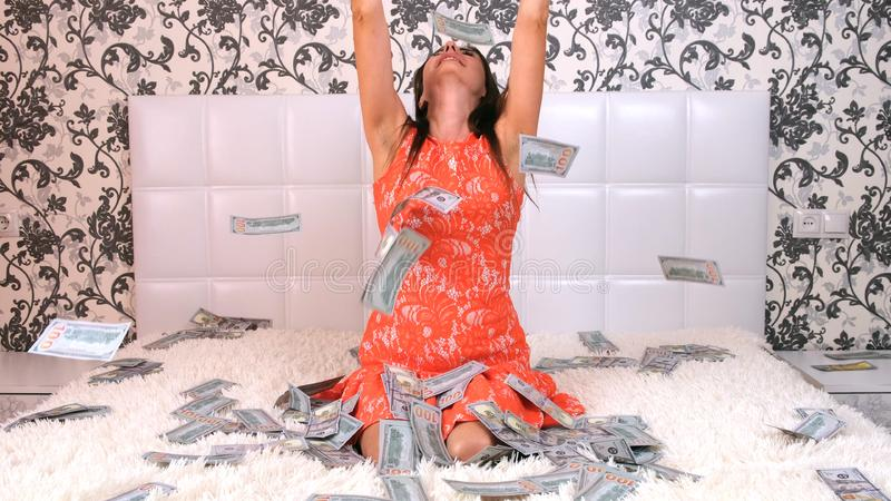 A lot of money, a view from the top, a girl in a cropped dress collects them. Throws, rejoices. Lies in the money they. Fall on her from the top stock photo