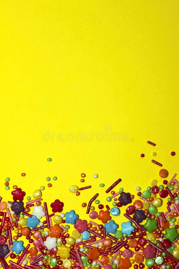 A Lot Of Multicolored Candy Sweets On Yellow Background. stock image