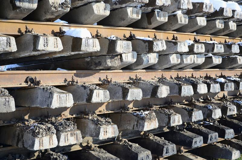 A lot of old rails and sleepers are stacked in a railway warehouse in winter. The concept of renewing a worn-out railway track royalty free stock images
