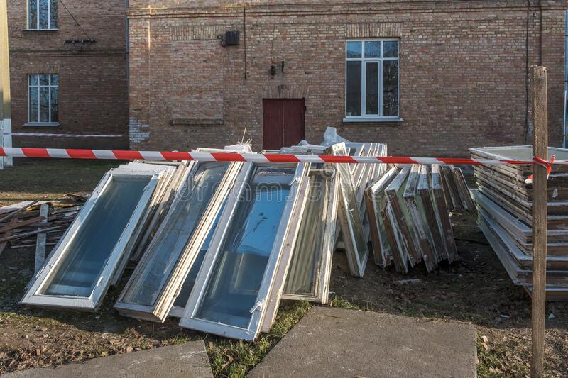 A lot of old wooden windows in the garbage outdoors near building, replacing with new pvc stock image