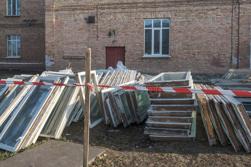A lot of old wooden windows in the garbage outdoors near building, replacing with new pvc stock photo
