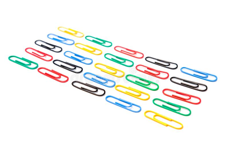 Colorful paper clips in white background. A lot of paper clips in the floor with white background royalty free stock images