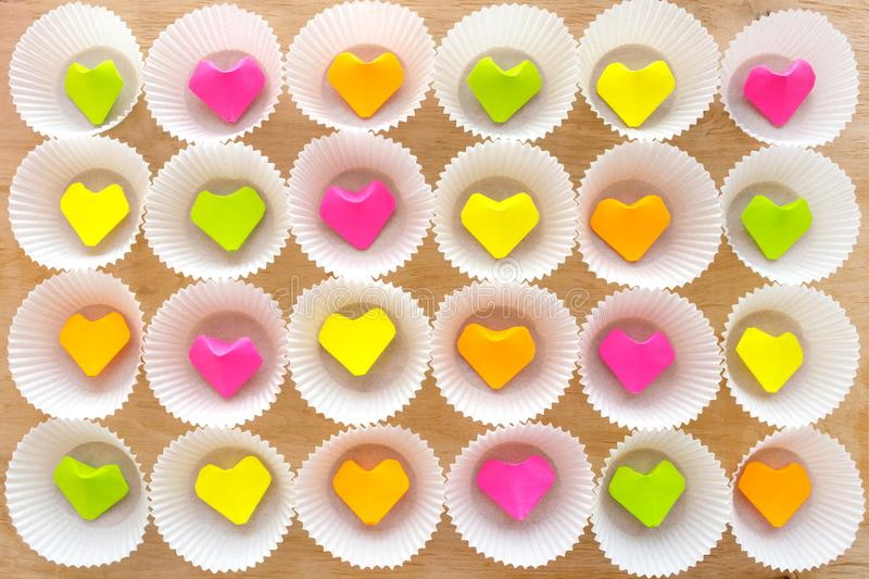 A lot of paper colorful origami heart in round white cupcake molds. Modern bright romantic background. Origami paper hearts stock images