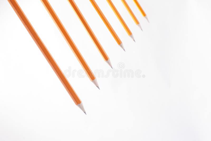 Lot of pencils ready to start drawing on white background. Abstract orange pencils line in space stock image
