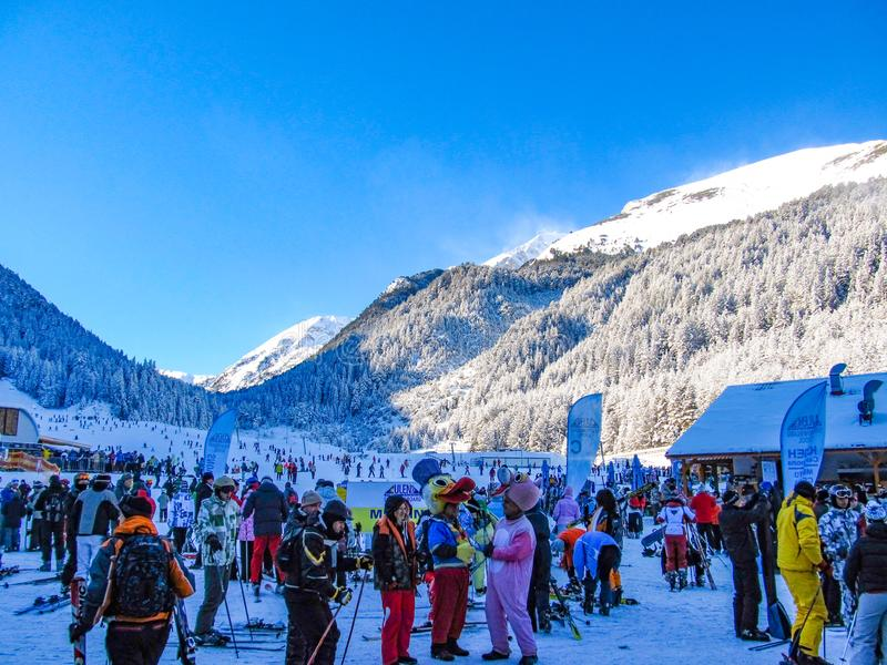 A lot of people in colorful clothes and various carnival costumes near the lift and slopes of the ski resort. Bulgaria, Bansko-. A lot of people in colorful stock image