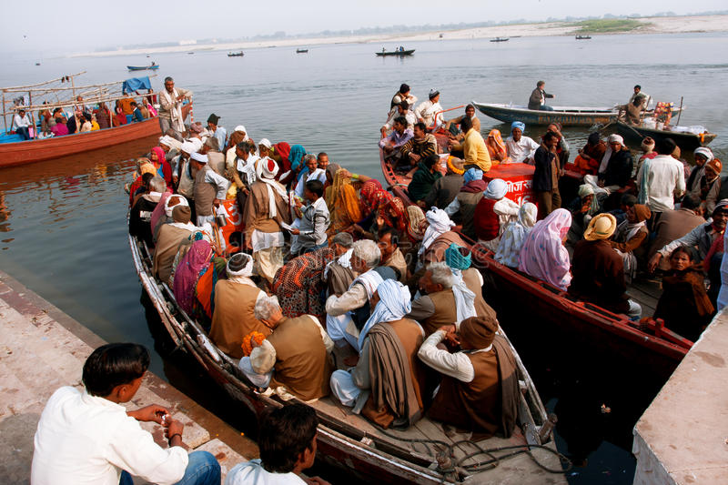 A lot of people sit on the crowded boats to cross the Ganges River stock photo