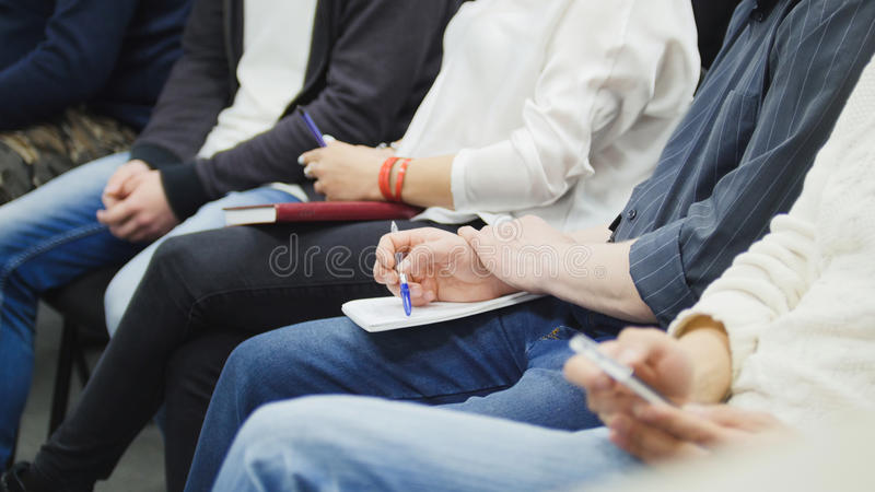 A lot of people sitting in business hall at lecture and taking notes - participators writing into their notebooks stock photography