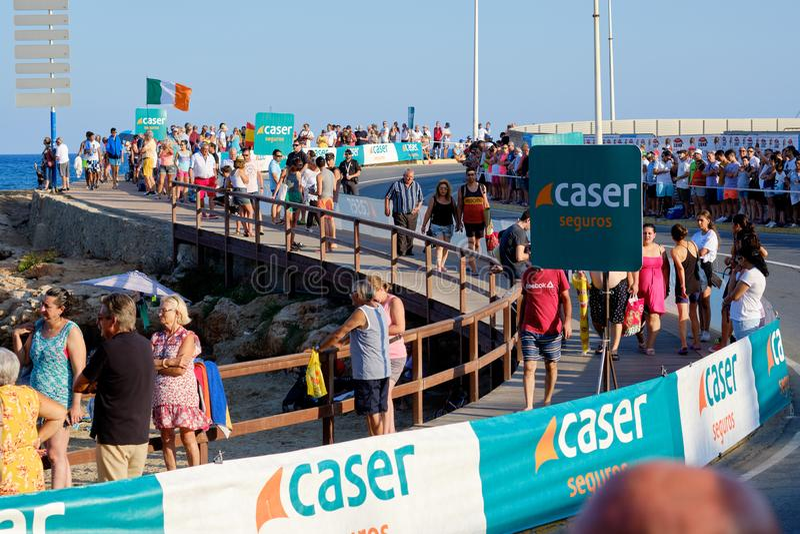 Lot of people walking along coastline near Mediterranean Sea during La Vuelta. Torrevieja, Spain - August 24, 2019: Lot of people walking along coastline near royalty free stock images