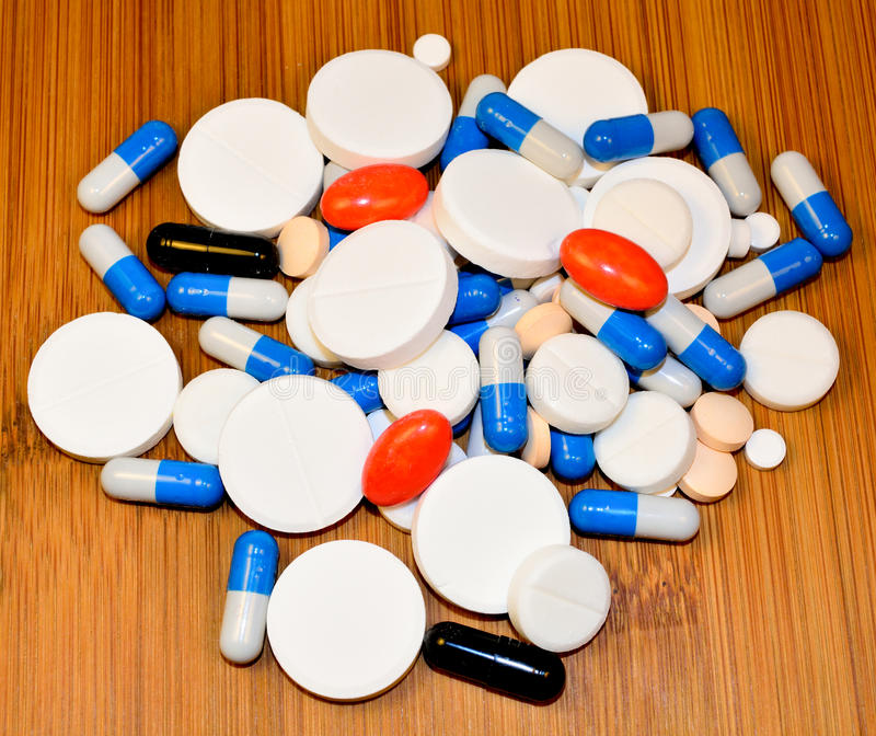 Medicine pills and capsules. A lot of pills and capsules on wooden background royalty free stock photos