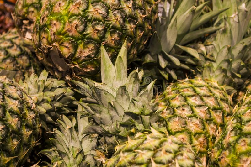A lot of pineapples in a market. Tropical fruit. Texture or background. Exotic. Vitamins. Healthy food. stock photos