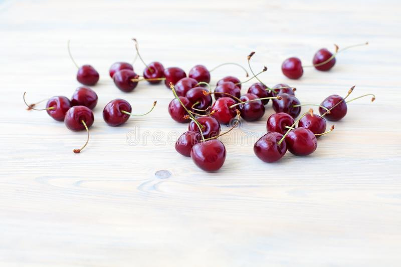 A lot of red berries of sweet cherry scattered on light wooden table close up, bunch of ripe cherry berries on white background stock images