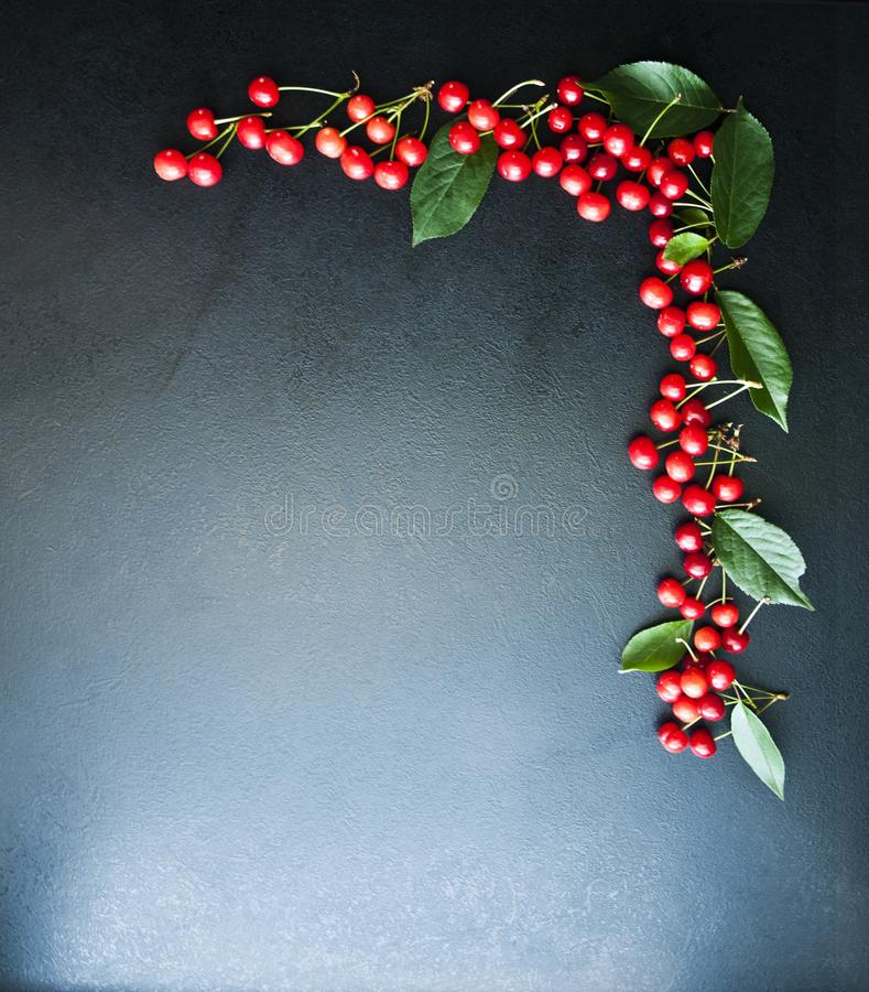 A lot of red cherries on a black background, royalty free stock images