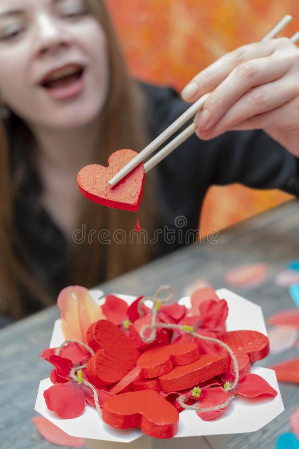 Girl holding a heart with chopsticks royalty free stock image