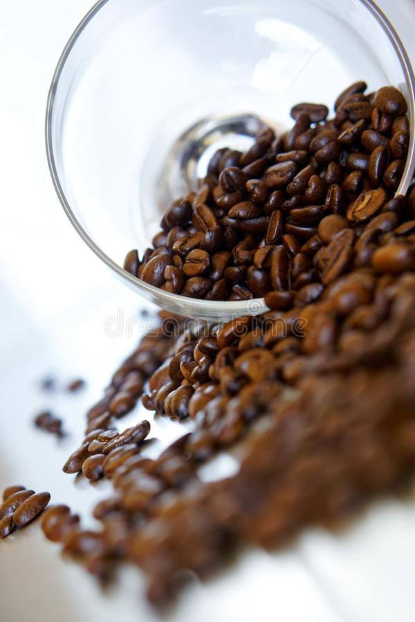 A lot of roasted beans of Arabica coffee are poured out of a transparent glass bowl. Light background. Daylight. Shallow depth of. Field. Vertical image stock photo