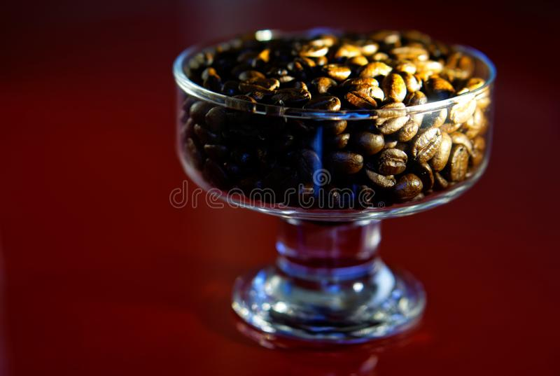 A lot of roasted beans of Arabica coffee in a transparent glass bowl. Red background royalty free stock image