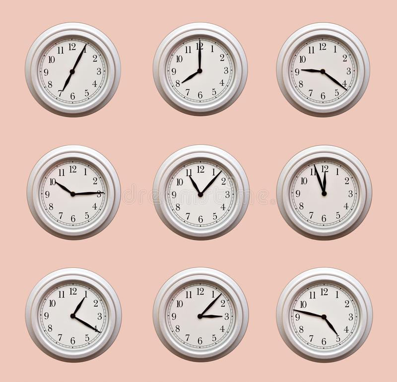 A lot of same clocks showing different times hanging on the pale orange wall royalty free stock photo