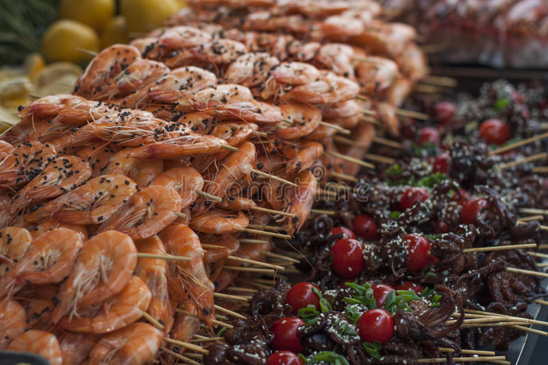 A lot of seafood on skewers, fried shrimp, octopus royalty free stock photography