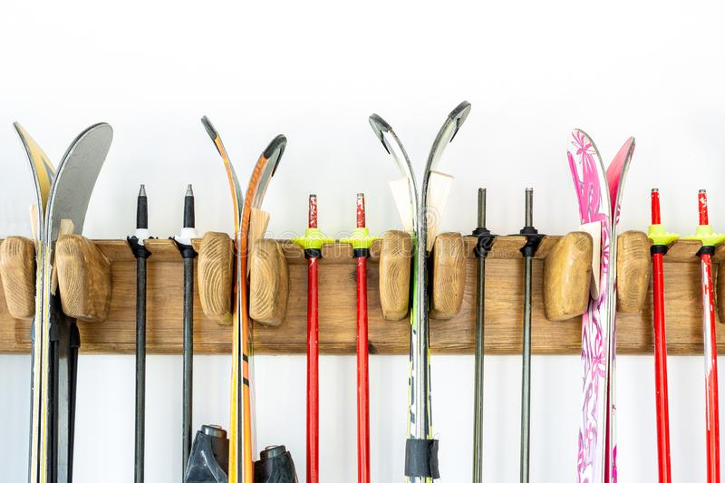 Lot of ski hanged on customized wooden wall mount at garage for seasonal storage. Extreme winter sport equipment handling at home royalty free stock photography