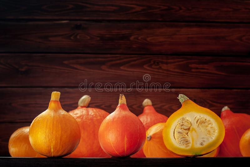 A lot of small orange and yellow pumpkins. At the bottom of the frame on a background of brown boards. One pumpkin is cut. Seeds are visible inside. Selective stock images