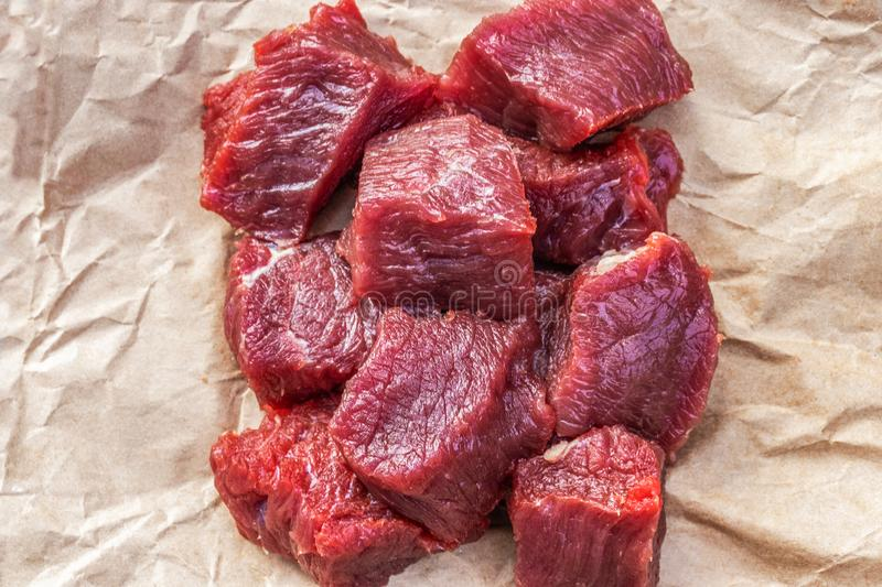 A lot of small pieces of raw beef meat on food paper. Side view from above, close-up royalty free stock photo