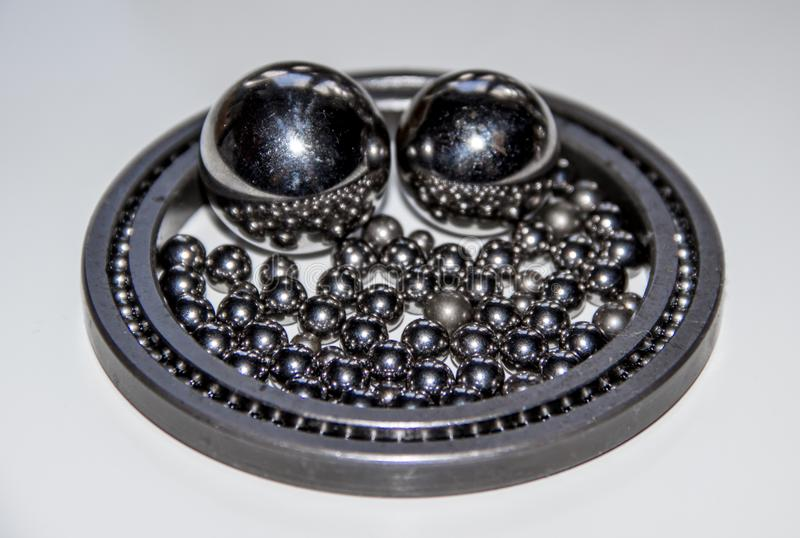 A lot of small stainless balls mirroring in a pair of big stainless balls within a slim ball bearing with selective focus. A lot of small stainless balls stock image
