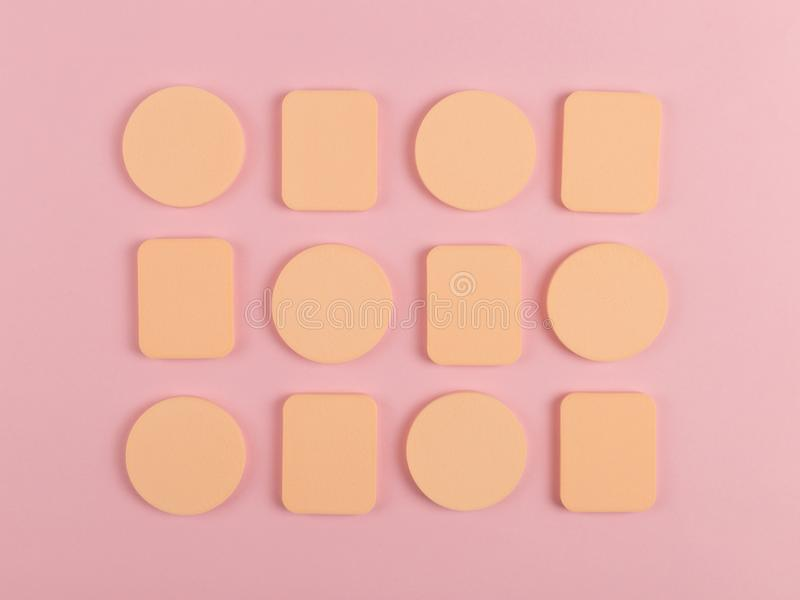 A lot of sponge, a beautiful blender for applying foundation or powder. Flat lay on a pink background, copy space. Square, nobody, texture, makeup, base stock photos