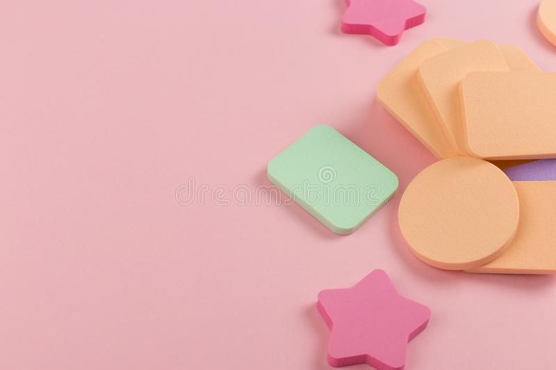 A lot of sponge, a beautiful blender for applying foundation or powder. Flat lay on a pink background, copy space. Square, nobody, texture, makeup, base stock photography