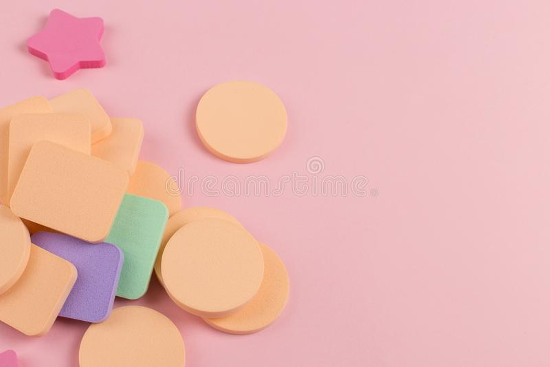 A lot of sponge, a beautiful blender for applying foundation or powder. Flat lay on a pink background, copy space. Square, nobody, texture, makeup, base royalty free stock images