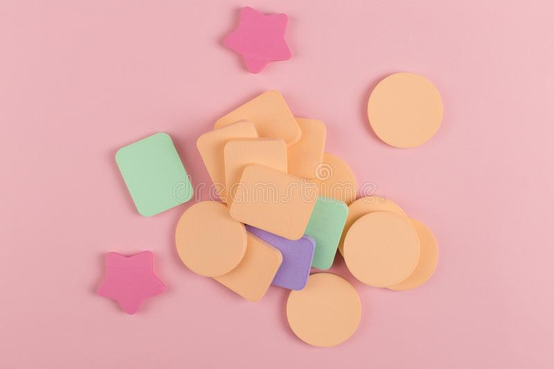 A lot of sponge, a beautiful blender for applying foundation or powder. Flat lay on a pink background, copy space. Square, nobody, texture, makeup, base royalty free stock photos