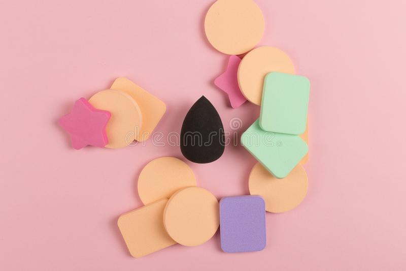 A lot of sponge, a beautiful blender for applying foundation or powder. Flat lay on a pink background, copy space. Square, nobody, texture, makeup, base royalty free stock image