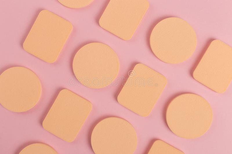 A lot of sponge, a beautiful blender for applying foundation or powder. Flat lay on a pink background, copy space. Square, nobody, texture, makeup, base stock image