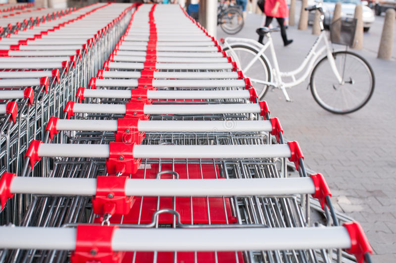 Lot of store carts. And bike parked in front of supermarket stock photography