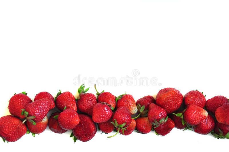 A lot of strawberry berries on a white background. A group of sweet fruits. Vitamin fruits for smoothies, cocktails and preserves. royalty free stock photo