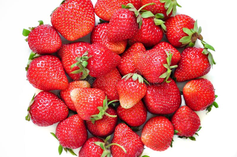 A lot of strawberry berries on a white background. A group of sweet fruits. Vitamin fruits for smoothies, cocktails and preserves. stock image