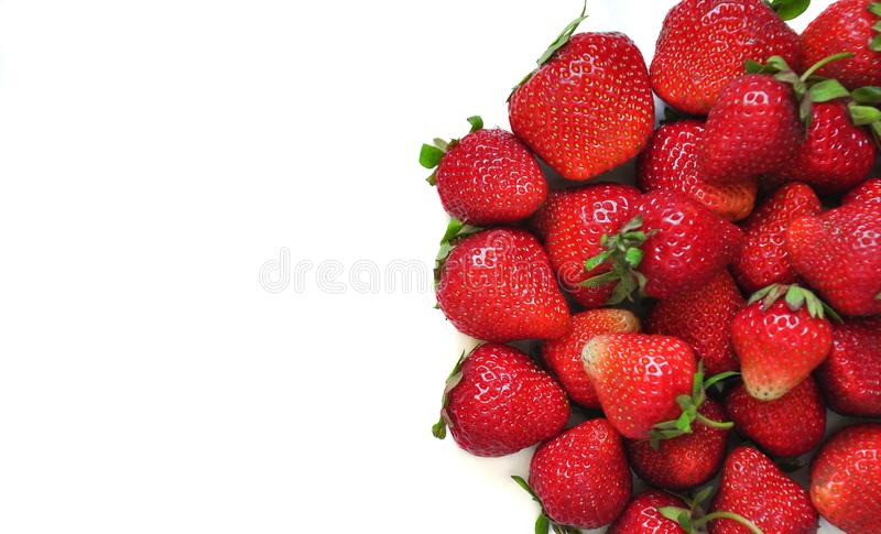 A lot of strawberry berries on a white background. A group of sweet fruits. Vitamin fruits for smoothies, cocktails and preserves. stock photos