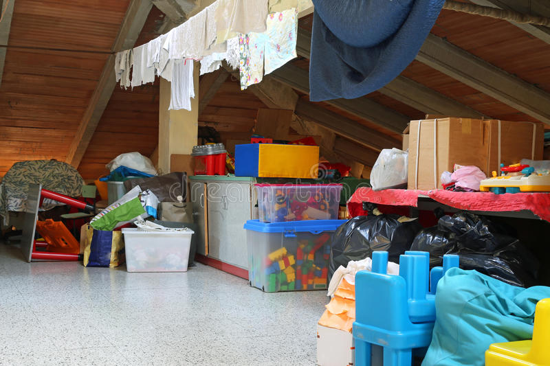 Lot of stuff and clothes hanging in the attic. Of a nursery school stock image