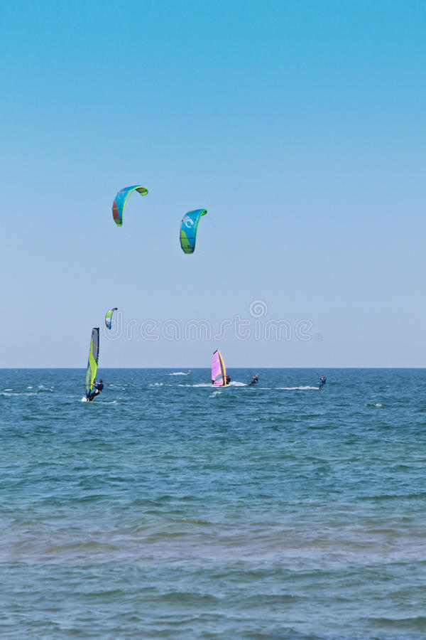 A lot of surfers and kite surfs stock photo