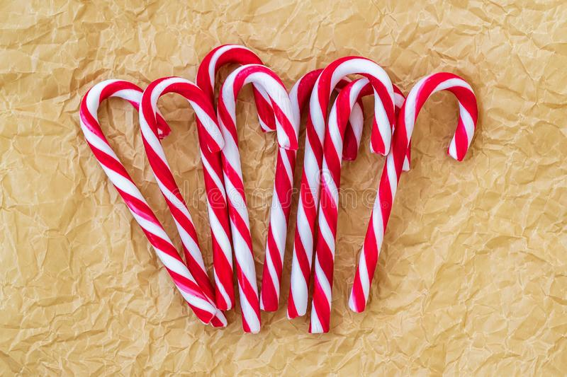 A lot of sweet caramel candy canes on a crumpled parchment paper. Tasty decorative attribute of Christmas and New Year royalty free stock photo