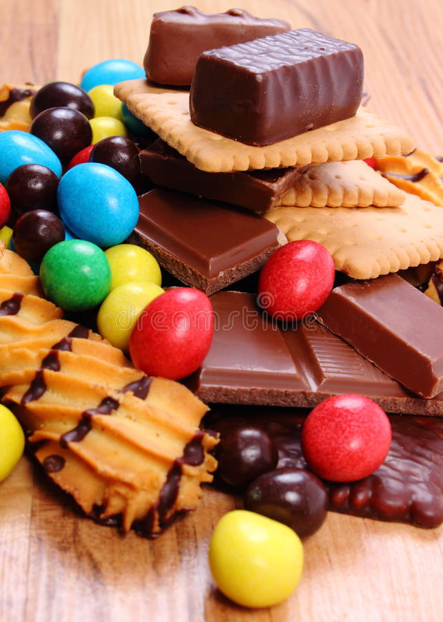 A lot of sweets on wooden surface, unhealthy food stock photography
