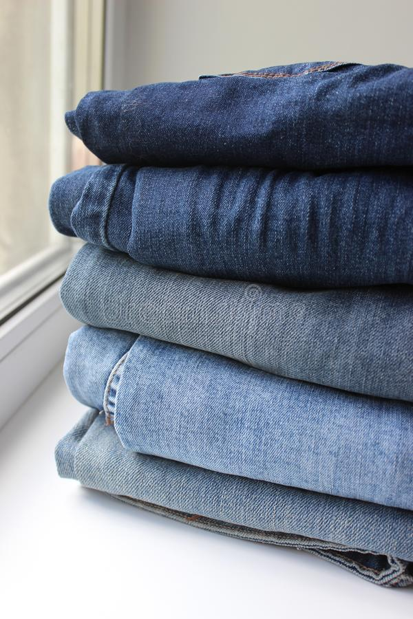 Blue jeans stacked in a pile on white background royalty free stock photo