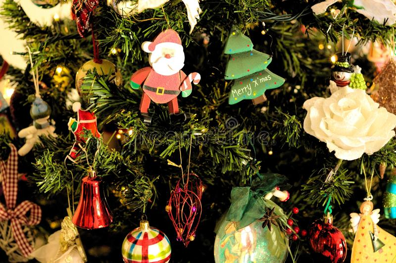 A lot of things are hanging on the Christmas tree: Santa Claus, Bells and Balls, Gingerbread man and Candy canes, Snowman. A lot of things are hanging on the stock images