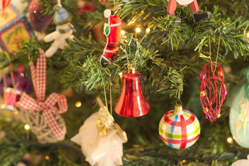 A lot of things are hanging on the Christmas tree: Santa Claus, Bells and Balls, Gingerbread man and Candy canes, Snowman. A lot of things are hanging on the stock photography