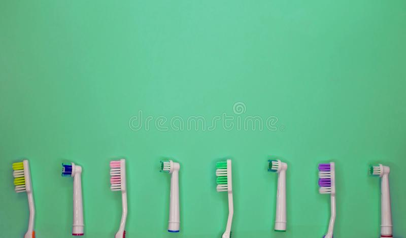 A lot of toothbrushes lie on aquamarine background. Top view, flat lay stock image