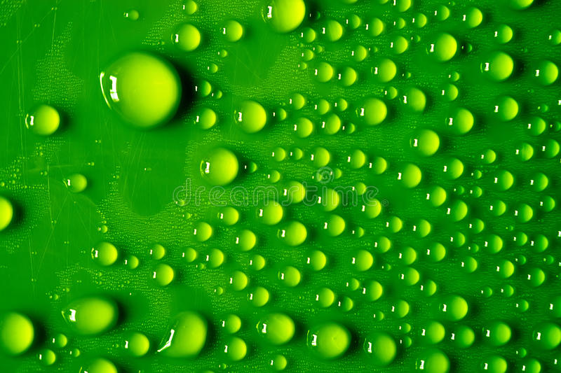 A lot of transparent water droplets on a bright green plastic surface, with scratches. Macro.  stock photos