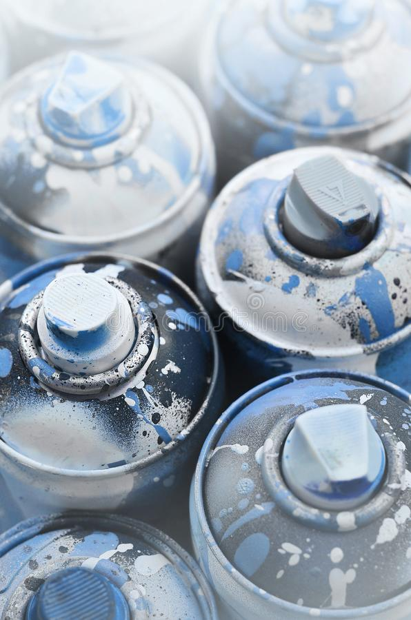 A lot of used spray cans of paint close-up. Dirty and smeared cans for drawing graffiti. The concept of a sweeping and careless d royalty free stock photos