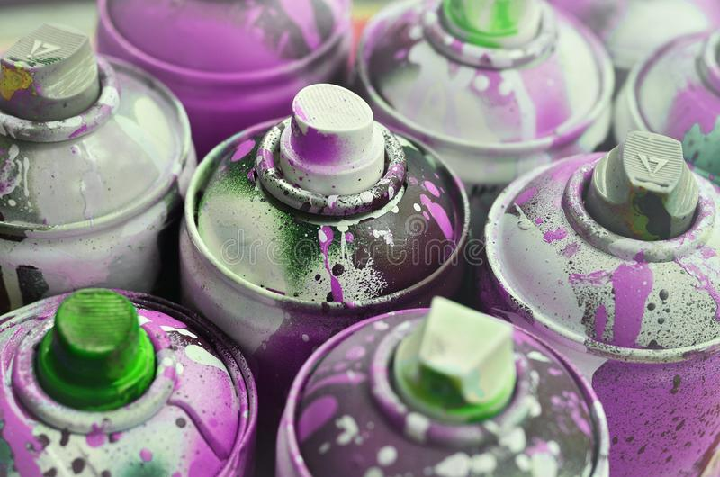 A lot of used spray cans of paint close-up. Dirty and smeared cans for drawing graffiti. The concept of a sweeping and careless d stock images