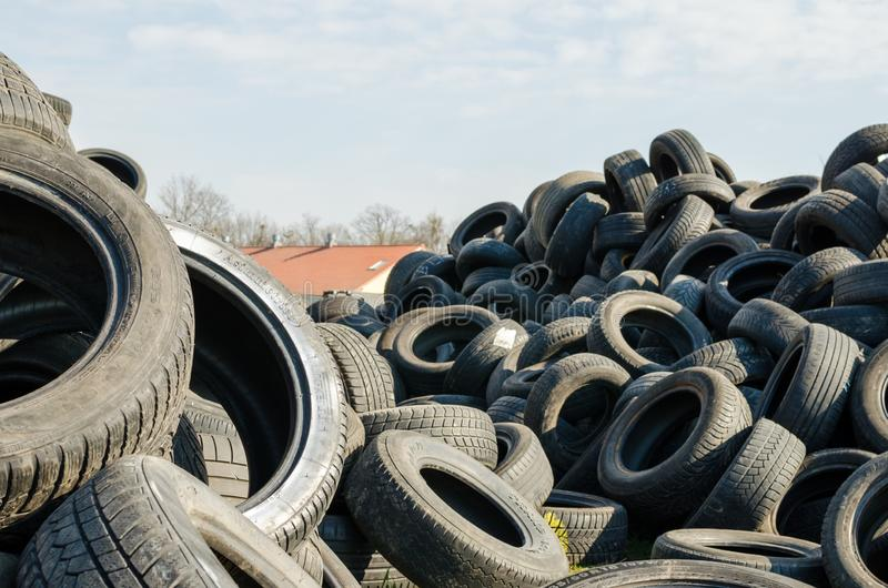 A lot of used tyres against roof of the house and blue sky with white clouds.  royalty free stock photo